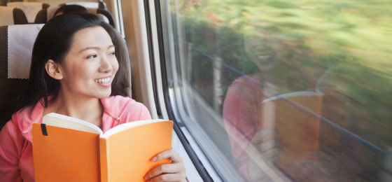 Asian woman smiling on a train with a book